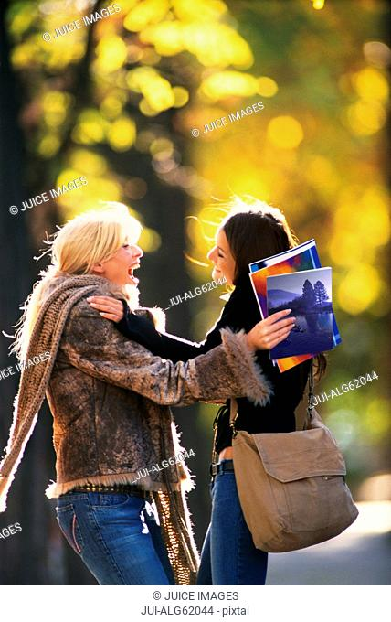 Excited friends greeting each other outdoors in Autumn