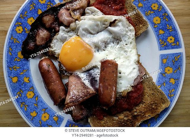 Breakfast of Smoked Bacon, Sausages, Fried Egg and Brown Wholewheat Toast