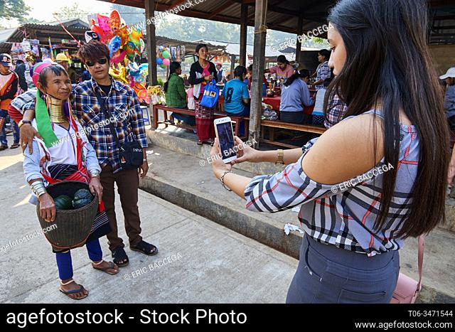 """Burmese tourists, young woman taking a picture of her friend together with a Kayan Lahwi woman. The"""""""" Long Neck"""""""" Kayan (also called Padaung in Burmese) are a..."""