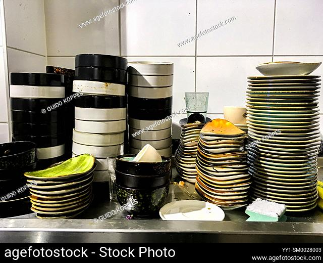 Tilburg, Netherlands. Multiple stacks of dirty disches to be cleaned and washing inside a restaurant's kitchen