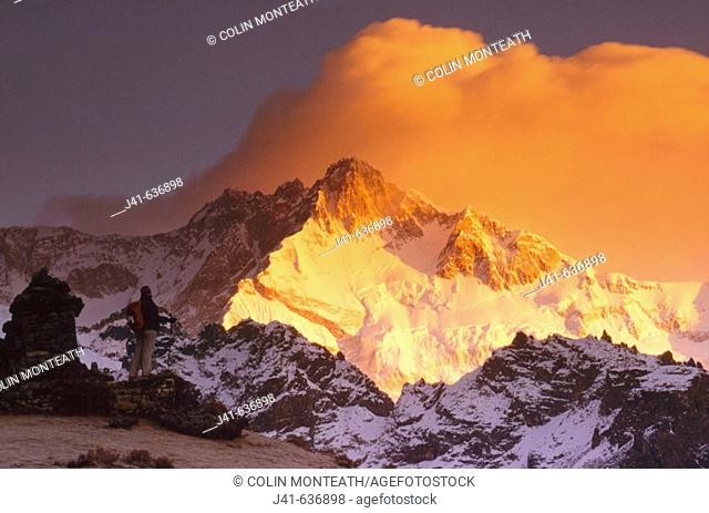 Trekker at dawn on Kangchenjunga (8595 metres), Talung face from Dzong Ri, Sikkim, India. Most easterly of the 8000 metre peaks