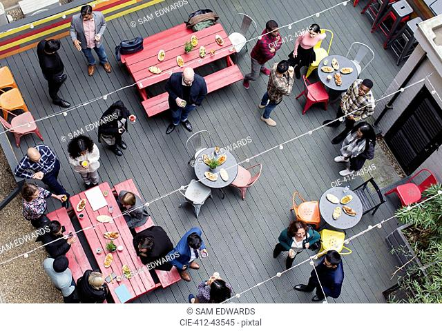 Overhead view friends socializing, drinking and eating at party on patio