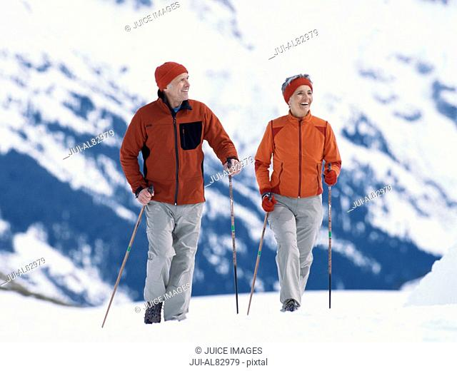 Senior couple walking with ski poles in snow
