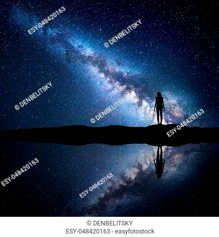 Milky Way. Night starry sky and silhouette of a standing woman on the mountain near the lake with sky reflection in water
