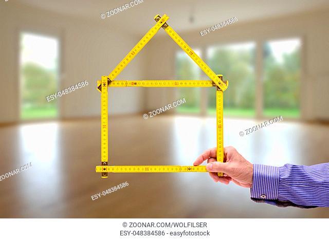 Meterstab symbolisch als Modellhaus im Wohnzimmer