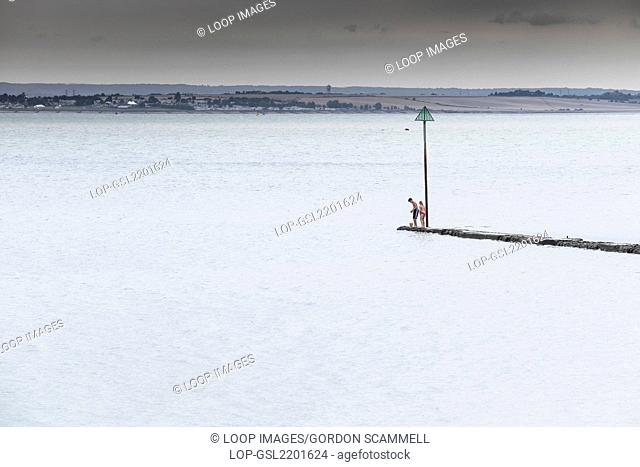 Children stand on the end of a breakwater in the Thames Estuary at Southend in Essex