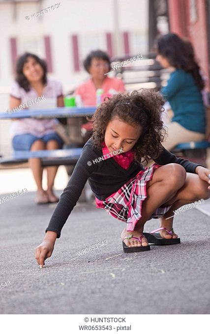 Hispanic girl drawing on the floor with chalk