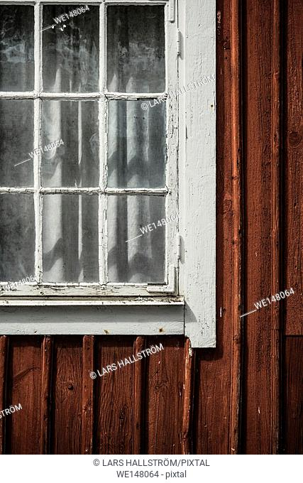 Window of red cabin. Old building exterior, Sweden