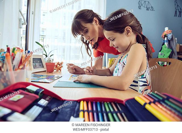 Mother helping girl doing her schoolwork at home