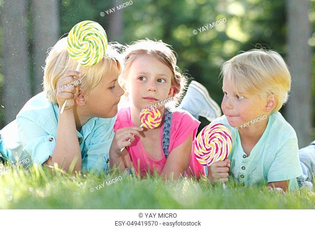 Group of happy children eating lollipops outdoors in summer park