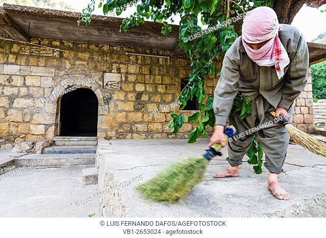 A Yezidi volunteer helps cleaning on the Lalish temples after Wednesday celebrations. Wednesday is the holy day for the practitioners of the Yezidi faith