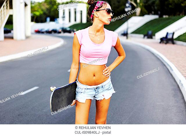 Portrait of young woman standing in street, holding skateboard