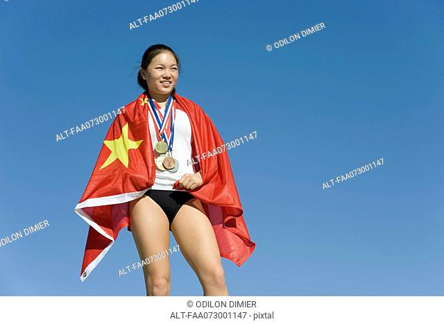 Female athlete on winner's podium, wrapped in Chinese flag
