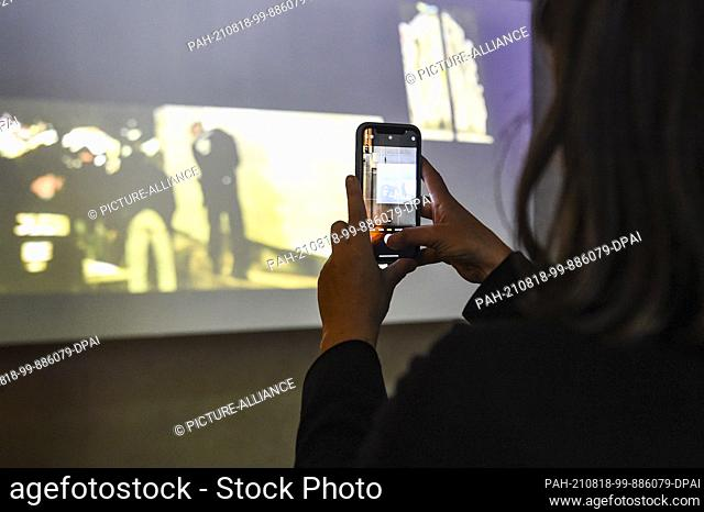 """18 August 2021, Berlin: A visitor photographs with her mobile phone the installation of a video by Eduard Freudmann entitled """"""""Shame Watch"""""""""""