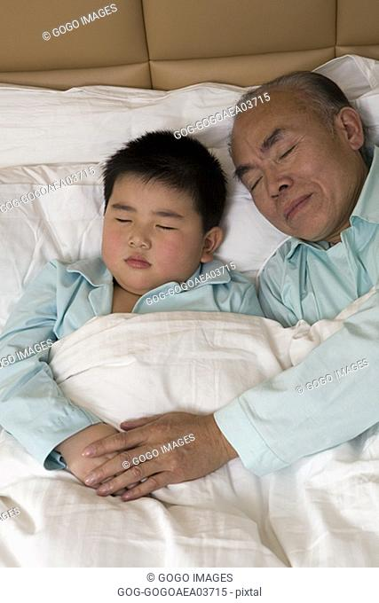 Middle-aged man and grandson asleep in bed