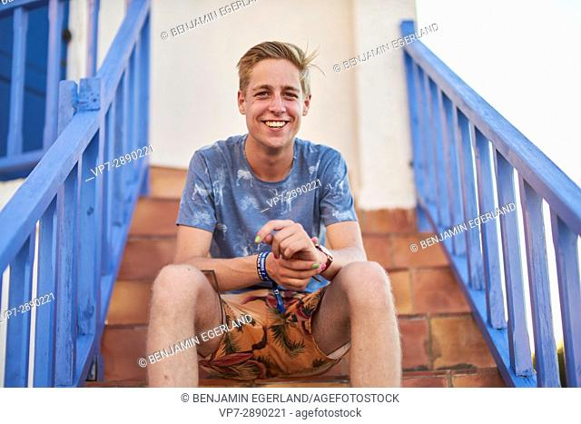 portrait of happy young man in leisure clothes sitting on stairs