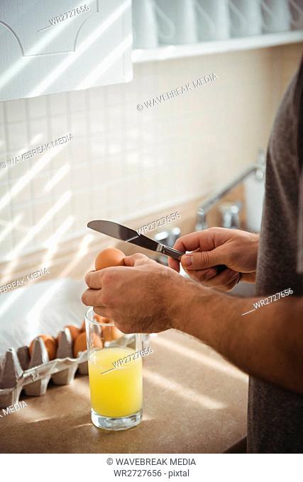 Man cracking an egg into a glass
