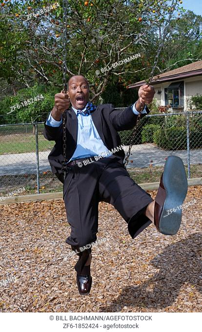 Black african american man in 40s dressed in business suit having so much fun on swing in park with no business stress