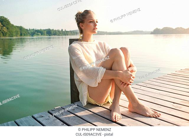Young woman sitting on lake pier