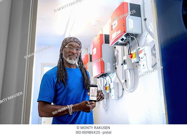 Community worker using smartphone app to check heat pump energy controls