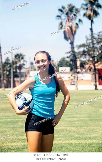Portrait of schoolgirl soccer player holding soccer ball on school sports field