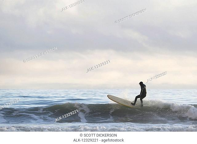 Man catching a wave while surfing, Southeast Alaska; Yakutat, Alaska, United States of America