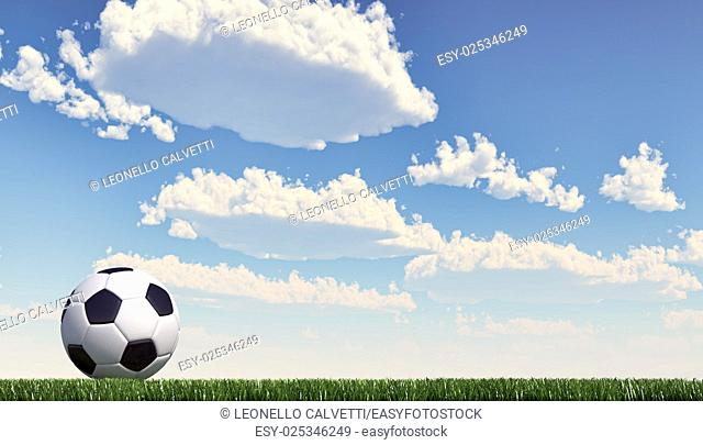 Soccer/football ball close up on grass lawn. Panoramic format. The ball stands on the left. Viewed from ground level, with white fluffy clouds sky in the...