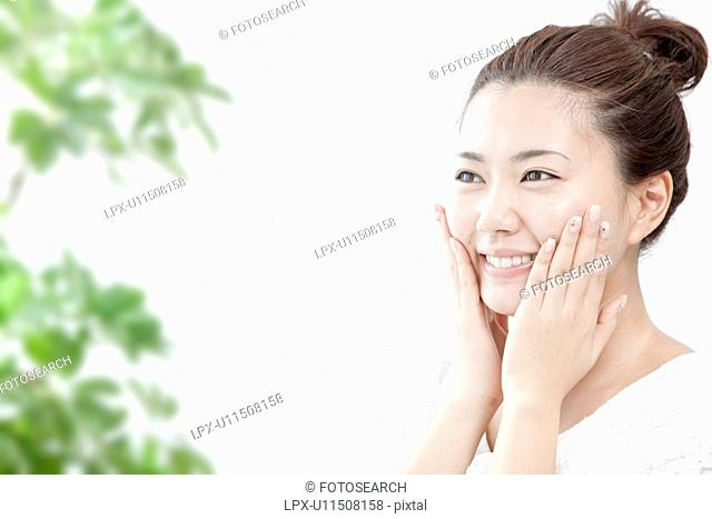 Young woman massaging her face, Tokyo Prefecture, Honshu, Japan