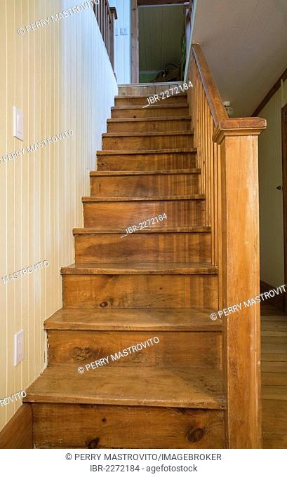 Wooden staircase in the dining room leading to the upstairs floor in an old Canadiana cottage-style residential fieldstone home, circa 1832, Laurentians, Quebec