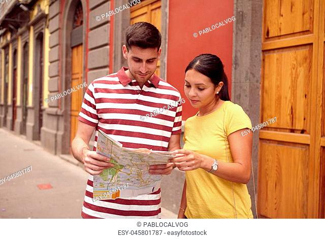 Young couple studying a map while smiling happily and dressed casually in t-shirts with old buildings behind them