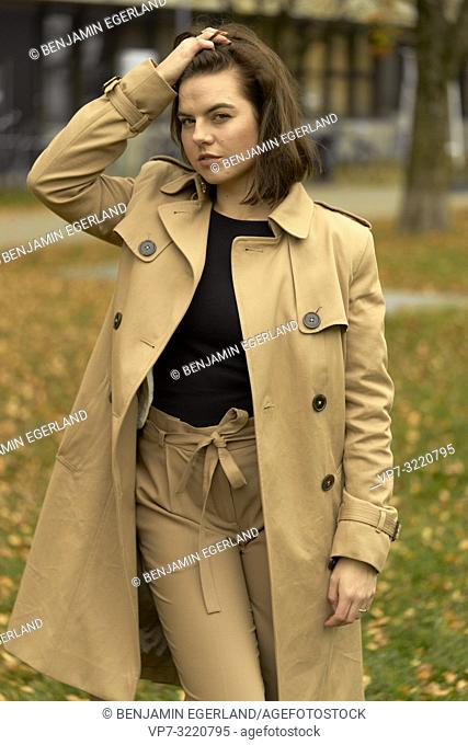 young woman walking outdoors in park during autumn season, ruffling hair, wearing coat, prankish, coquettish, in Munich, Bavaria, Germany
