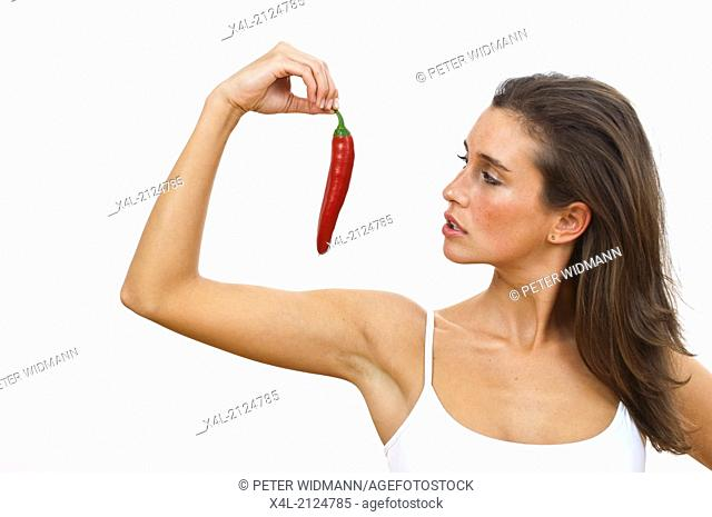 Young woman staring at a red pepper (model-released)