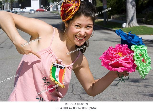 Woman holding flowers and pointing at Mexican flag