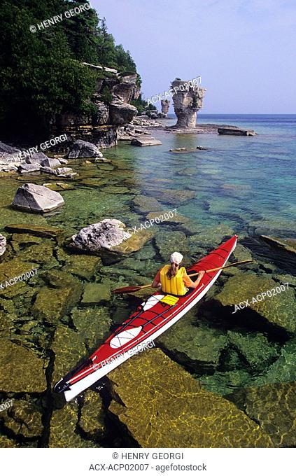 Young woman sea kayaking past Flowerpot Island, Fathom Five National Marine Park, Ontario, Canada