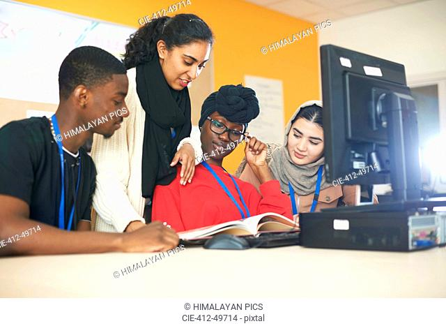 Multi-ethnic college students studying at computer in computer lab