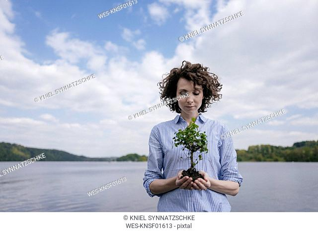 Woman at lake holding little tree in her hands