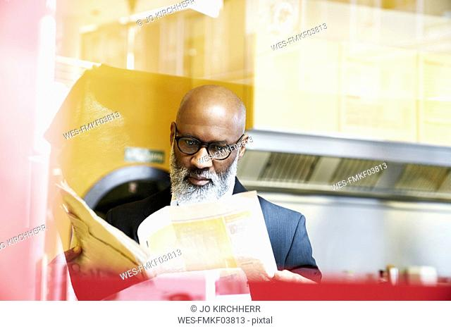 Mature businessman sitting in snack bar, reading newspaper