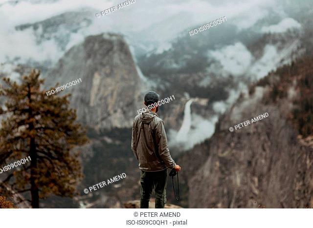 Hiker enjoying view of fog covering valley, Yosemite National Park, California, United States