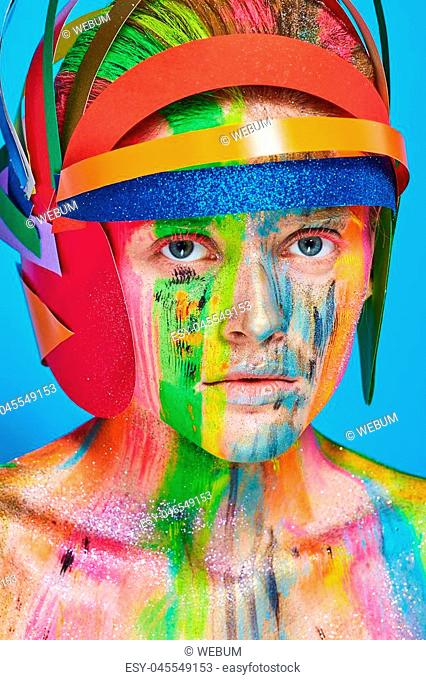 Model with colorful abstract makeup in multicolored helmet on blue background
