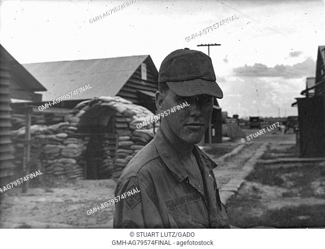 A photograph a United States Army serviceman wearing his jungle jacket, cap and a stoic expression, wooden buildings and a sandbag reinforced structure are...