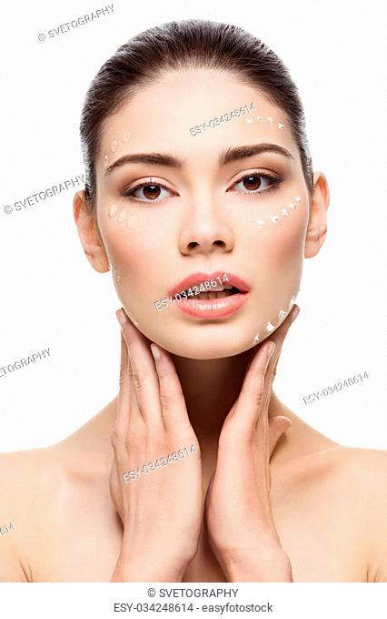 Beautiful young woman with foundation cream on face. Beauty shot. Isolated over white background. Copy space