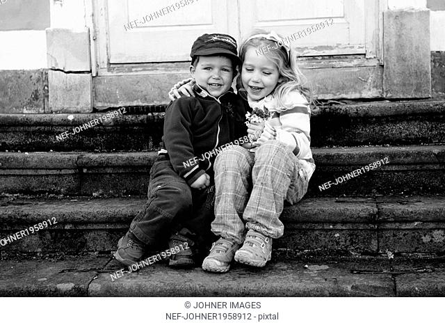 Brother and sister sitting on doorstep