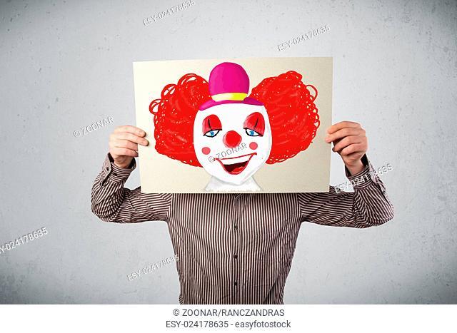 Businessman holding a cardboard with a clown on it in front of his head