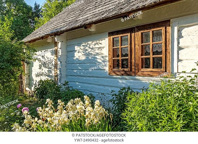 Flower garden in front of an old house, Tokarnia open-air museum, Poland