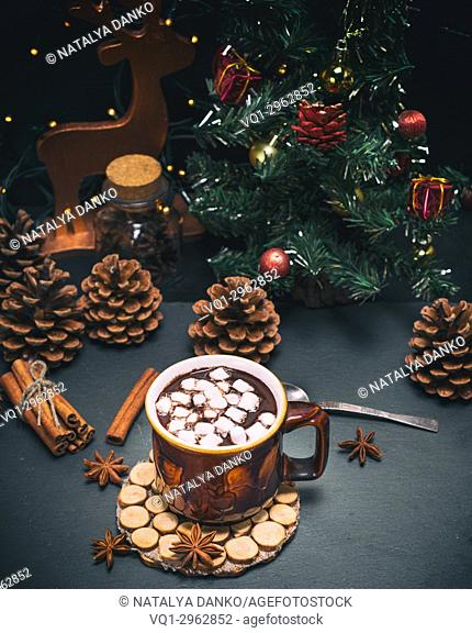 hot chocolate with marshmallows in a brown mug on a black background, behind a christmas decor
