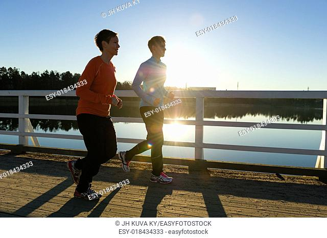 Two women jogging together along the bridge at sunrise