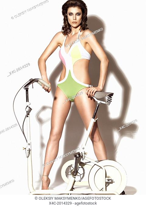 Fashion portrait of a beautiful slim woman wearing one-piece swimsuit standing behind a retro exercise bicycle isolated on white background