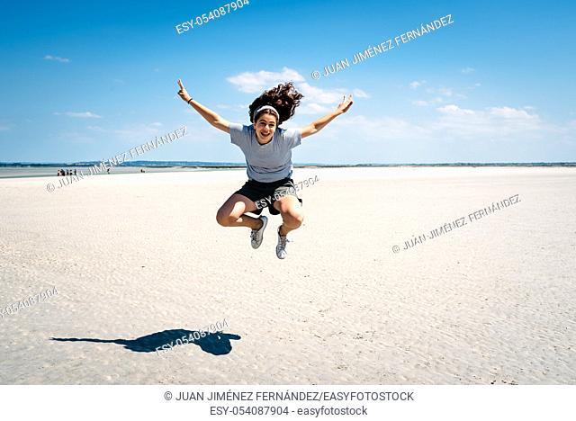 Full-length portrait of joyful female traveler jumping on the beach in the bay of Mont Saint-Michel