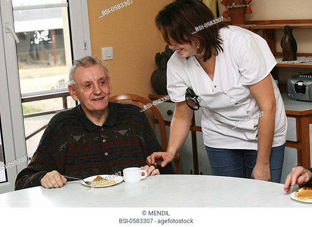 HOME FOR THE AGED Photo essay in a nursing home for the elderly in the department of Aisne, France. Nurse's aide with a retired man having his afternoon tea