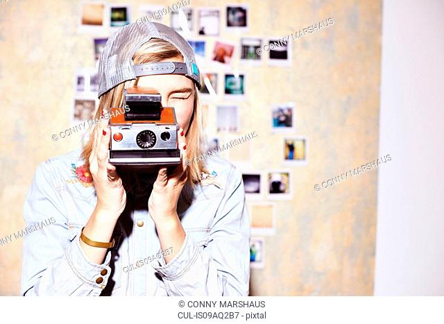 Young woman in front of photo wall taking photograph on retro camera